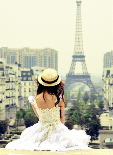 Photography of a girl in a summer dress looking at the Eiffel Tower in the distance