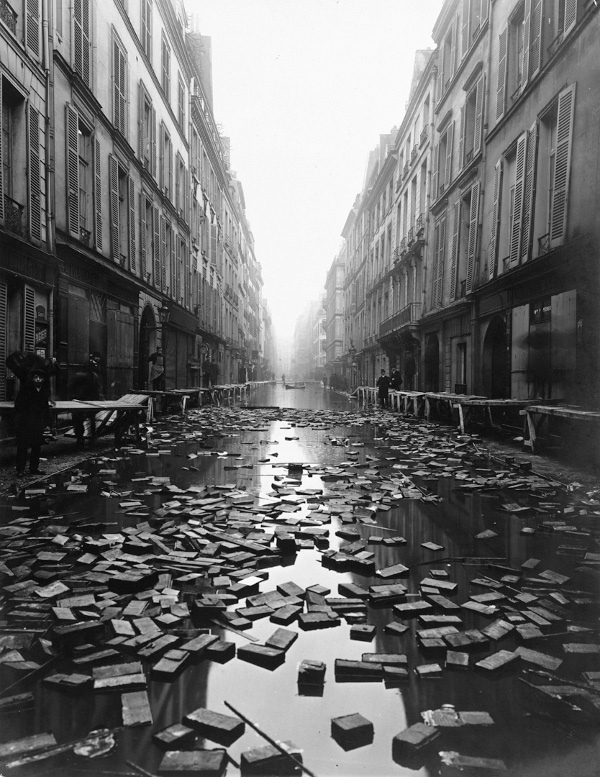 Black and white photography showing a flooded street with books after the great flood in Paris, France in 1910