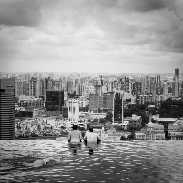 infinity swimming pool overlooking roofs of singapore black and white photography water architecture buildings horizon city