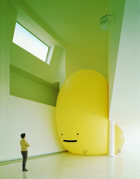 large yellow smile ball ballon squeezed into interior space architecture photography fun funny cute colourful design idea innovative