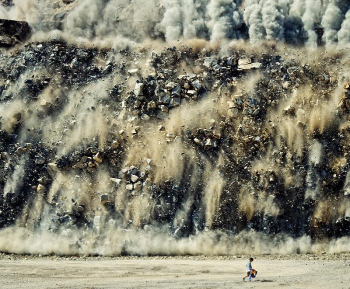rock-slide explosion destruction demolition building debris kid child walking in front of falling rubble smoke