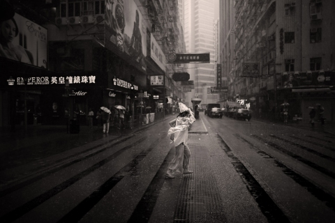 black and white vintage street architecture photographer city architecture wind rain girl covering with newspaper protecting from storm