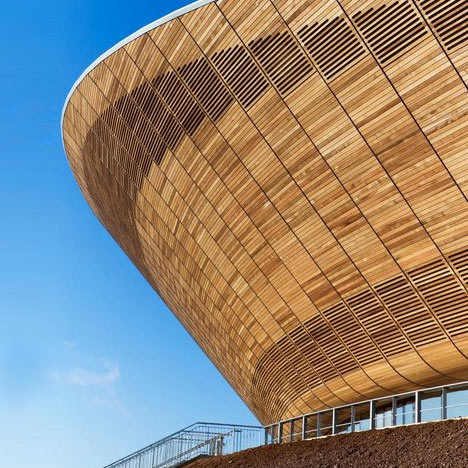 velodrom london olypmics games stadium biking bicycle arena timber architecture facade sloping organic curve beautiful architectural photography London firm Hopkins Architects have completed the Velodrome, the first of the five permanent venues on the Olympic Park for the London 2012 Olympic Games. The hyperbolic paraboloid-shaped steel-framed structure sits on a 360 degree glazed concourse at entry level, and is clad in timber with little apertures to allow for natural ventilation. The lightweight, double-curving, cable-net roof structure was designed to reflect the shape of the cycling track. 6,000 seats are located all the way around the track and are split into an upper and lower tier by the glazed concourse. 48,000 cubic metres of material was excavated to create the bowl in which the building sits. The London 2012 Velodrome will host the Olympic and Paralympic indoor cycling events and also includes changing rooms, retail facilities, workshop and a viewing concourse.