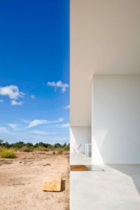 modern architecture blog architectural artistic photography website wordpress tumblr best great blog top sky white minimalistic architecure house japanese Here's another classic villa from the studio of Marià Castelló Martínez, like their others we've covered, also on the island of Formentera. In Es Pujol De Sera they realise their contemporary version of the spare architectural tradition of Formentera. Set far from the sea in the inland region, one entire side of the compact and simple live/work space houses an architecture studio. The program is work on one side, live on the other. Even the plan displays the austere geometry that is their signature. The spacious studio provides an unhurried setting for devising thoughtful architecture. The working side of the house is just as open and inviting as the basking and lazing side. Very spare and dry detail makes even bedrooms not too private, should clients happen upon the live side of the live work space. The villa is surrounded by the smell of rosemary, and is set in a region with wheat and barley fields. The topography inland is flat and the inertia of these surroundings is reflected in the flat affect of the villa itself. But, by not distracting, these spare surroundings help create the wandering and dreamy space that helps in assessing creative design work like modelling architectural ideas. Iroko timber and glass are used down the length of this central divider/service unit that separates the working from the living area. A small setback around the edge in section creates the sensation that the building is floating over the site to transition between the manmade and the natural environment. Even island paradises can have a tumultuous climate, especially in winter. But this will weather it. Perhaps in several centuries, the good bones of this spare structure will have aged to resemble the surrounding artefacts. (Both this bed and the guest bed are Murphy beds that can be placed up against the central wall in the da