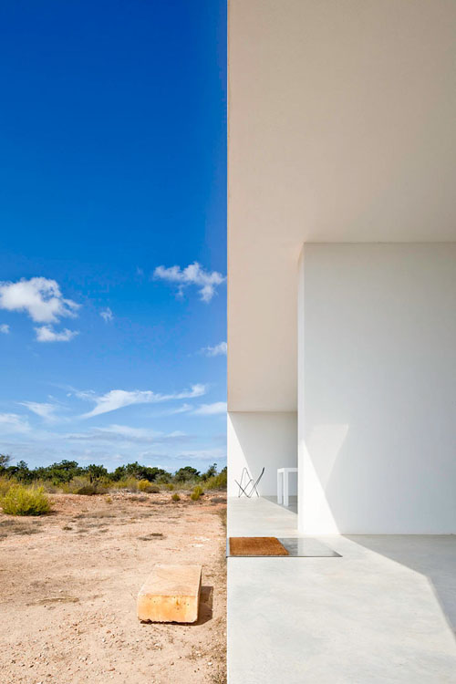 Here's another classic villa from the studio of Marià Castelló Martínez, like their others we've covered, also on the island of Formentera. In Es Pujol De Sera they realise their contemporary version of the spare architectural tradition of Formentera. Set far from the sea in the inland region, one entire side of the compact and simple live/work space houses an architecture studio. The program is work on one side, live on the other. Even the plan displays the austere geometry that is their signature. The spacious studio provides an unhurried setting for devising thoughtful architecture. The working side of the house is just as open and inviting as the basking and lazing side. Very spare and dry detail makes even bedrooms not too private, should clients happen upon the live side of the live work space. The villa is surrounded by the smell of rosemary, and is set in a region with wheat and barley fields. The topography inland is flat and the inertia of these surroundings is reflected in the flat affect of the villa itself. But, by not distracting, these spare surroundings help create the wandering and dreamy space that helps in assessing creative design work like modelling architectural ideas. Iroko timber and glass are used down the length of this central divider/service unit that separates the working from the living area. A small setback around the edge in section creates the sensation that the building is floating over the site to transition between the manmade and the natural environment. Even island paradises can have a tumultuous climate, especially in winter. But this will weather it. Perhaps in several centuries, the good bones of this spare structure will have aged to resemble the surrounding artefacts.<br />(Both this bed and the guest bed are Murphy beds that can be placed up against the central wall in the daytime.)