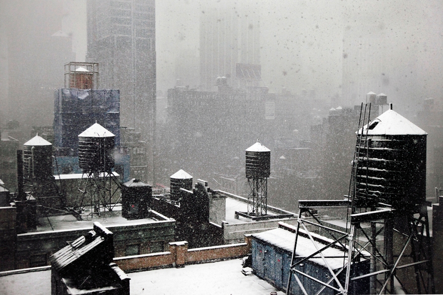 Photography of New York City roofs of buildings covered in snow USAduring winter manhattan architecture urban city water tanks roofs old covered in snow snowing cold chill