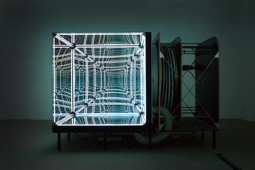 "In this cube installation based on the principle of one way mirror or "" spy glass "" three out of six surfaces of the cube are made of flexible membrane with air tank and a compressor connected to it. By inflating or deflating the air tank, the membrane turns convex or concave, deforming the reflections."