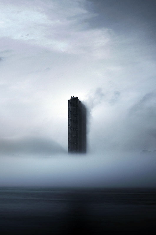 Beautiful black and white photograph of a lonely skyscraper standing amongst the clouds and mist architecture light dark mist fog moody atmosphere