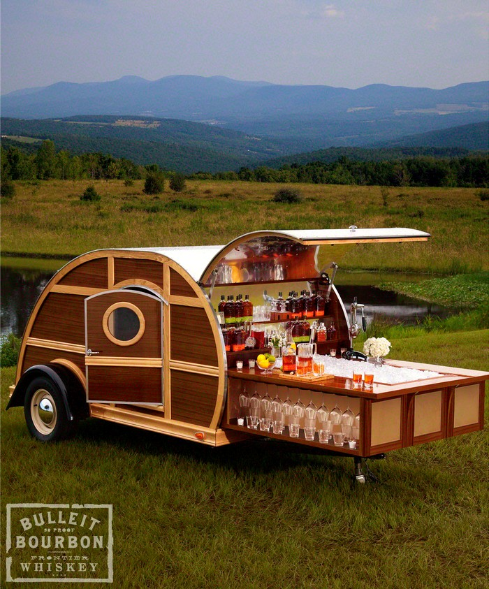 A chorus of cheers rings out the minute you pull up. Tailgating will never be the same now that your Bulleit Frontier Whiskey Woody-Tailgate Trailer is on the scene. Designed by interior designer Brad Ford, it's impressive on the outside, but what's on the inside truly astounds: sleek leather furnishings and details from Moore & Giles, rich wood finishings (handcrafted from reclaimed Bulleit Bourbon casks), elegant glassware, and a top-notch entertainment system, including a flat-screen TV, Blu-ray Disc™ player, and a state-of-the-art sound system, plus a one-year supply of Bulleit Bourbon and Bulleit Rye*. You park, open the hatch, and slide out the bar—cocktails anyone?  The details:      Two limited-edition trailers available. (First available for immediate delivery; second available within six months of placing order.)     Transportation and delivery of trailer is included within the continental United States.     Created by designer Brad Ford, who has more than 10 years of experience in interior design and was named one of America's Top Young Designers by House Beautiful and recognized as one of the Rising Stars of Interior Design by the International Furnishings and Design Association.     Moore & Giles, founded in 1933 in Lynchburg, Virginia, is dedicated to designing and developing the most luxurious natural leathers, working with tanneries worldwide and delivering unparalleled quality.     Entertainment system by Sony® and includes: TV, sound-bar speakers, receiver with touch screen, and smartphone controls.   10% percent of the proceeds from the purchase of the Bulleit Woody Party Trailer will benefit amfAR™, The Foundation for AIDS Research. For more information, call 1-877-9NM-GIFT.  *One-year supply of Bulleit Bourbon and Bulleit Rye not to exceed four cases of each, based on FDA average consumption.US United States USA Bulleit Frontier Whiskey Woody-Tailgate Trailer by Neiman Marcus teardrop camper camper van tear drop camping innovative cool design camper movable home vehicle car photography design blog on facebook tumblr wordpress