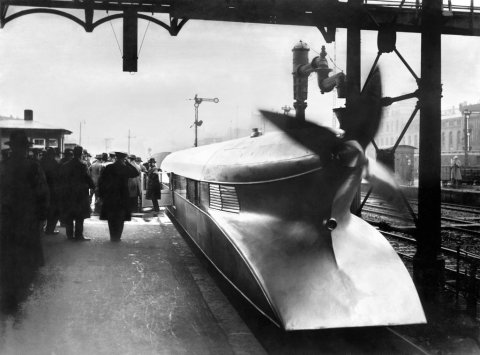 Vintage black and white photograph of a futuristic strange train design with a rotor blade engine and aerodynamic shape technology development history retro travel rail track design