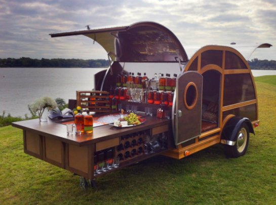 A chorus of cheers rings out the minute you pull up. Tailgating will never be the same now that your Bulleit Frontier Whiskey Woody-Tailgate Trailer is on the scene. Designed by interior designer Brad Ford, it's impressive on the outside, but what's on the inside truly astounds: sleek leather furnishings and details from Moore & Giles, rich wood finishings (handcrafted from reclaimed Bulleit Bourbon casks), elegant glassware, and a top-notch entertainment system, including a flat-screen TV, Blu-ray Disc™ player, and a state-of-the-art sound system, plus a one-year supply of Bulleit Bourbon and Bulleit Rye*. You park, open the hatch, and slide out the bar—cocktails anyone?  The details:      Two limited-edition trailers available. (First available for immediate delivery; second available within six months of placing order.)     Transportation and delivery of trailer is included within the continental United States.     Created by designer Brad Ford, who has more than 10 years of experience in interior design and was named one of America's Top Young Designers by House Beautiful and recognized as one of the Rising Stars of Interior Design by the International Furnishings and Design Association.     Moore & Giles, founded in 1933 in Lynchburg, Virginia, is dedicated to designing and developing the most luxurious natural leathers, working with tanneries worldwide and delivering unparalleled quality.     Entertainment system by Sony® and includes: TV, sound-bar speakers, receiver with touch screen, and smartphone controls.   10% percent of the proceeds from the purchase of the Bulleit Woody Party Trailer will benefit amfAR™, The Foundation for AIDS Research. For more information, call 1-877-9NM-GIFT.  *One-year supply of Bulleit Bourbon and Bulleit Rye not to exceed four cases of each, based on FDA average consumption.