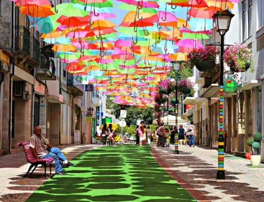 """Colorful Umbrella Art Installation These candy-colored umbrellas suspended over an Águeda street are present rain or shine. Installed by an as-yet-unidentified artist portuguese design studio ivotavares, the unique canopy lends a zany feel to the cobblestone Portuguese road. Flickr photographer  recently shot these great photos and she writes """"In July, in Águeda (a Portuguese town), some streets are decorated with colorful umbrellas. I felt like a kid, amazed by all that color!"""" She calls it Umbrella Sky."""