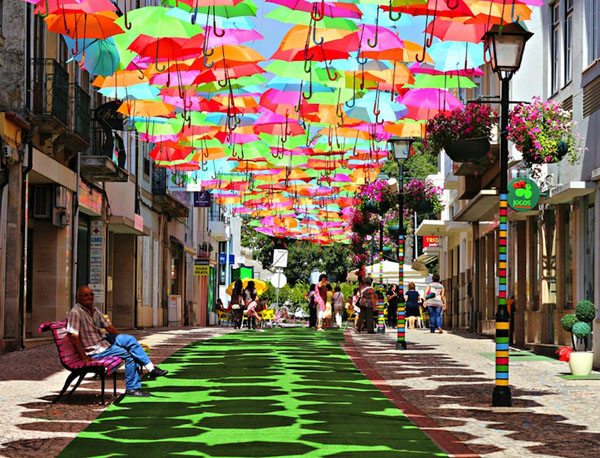 "Colorful Umbrella Art Installation These candy-colored umbrellas suspended over an Águeda street are present rain or shine. Installed by an as-yet-unidentified artist portuguese design studio ivotavares, the unique canopy lends a zany feel to the cobblestone Portuguese road. Flickr photographer  recently shot these great photos and she writes ""In July, in Águeda (a Portuguese town), some streets are decorated with colorful umbrellas. I felt like a kid, amazed by all that color!"" She calls it Umbrella Sky."