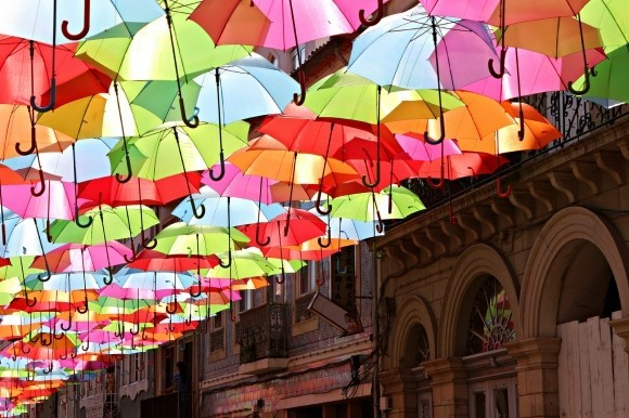colorful-umbrella-installation-agueda-portugal-patricia-almeida-gessato-gblog Photograph of suspended candy-colored umbrellas over an Águeda street in Portugal, by design studio Ivotavares / photographer  Patrícia Almeida