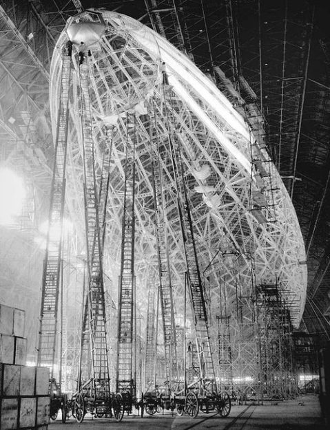 "'USS Macon (ZRS-5)- construction of a huge zeppelin carcass steel workers ladders gigantic construction architecture aerospace engineeringUSS Macon (ZRS-5) was an airship built and operated by the United States Navy for scouting. She served as a ""flying aircraft carrier"", launching Curtiss F9C Sparrowhawk biplane fighters. In service for less than two years, in 1935 Macon was damaged in a storm and lost off California's Big Sur coast.'"