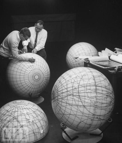 Scientists study the phases of the moon on lunar models in preparation for an eventual manned flight to moon. space travel black and white vintage photography