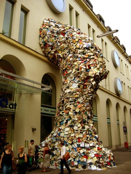 alicia-martin puking building. Artist Alicia Martin's tornado of books shoot out a window like a burst of water from a giant hose. The Spain-based artist's sculptural installation at Casa de America, Madrid depicts a cavalcade of books streaming out of the side of a building. The whirlwind of literature defies gravity and draws attention with its grandeur size. There have been three site-specific installations, thus far, of the massive sculptural works in this series known as Biografias, translated as Biographies, that each feature approximately 5,000 books sprawled out around and atop one another.  Martin's giant book structures give life to the inanimate objects filled with knowledge. By constructing the curving towers with a rather free and disheveled exterior, while maintaining a sturdy core, the books' loose pages are free to blow and rustle in the wind, allowing the piece to be further animated. Take a look at the short video, below, to see the piece in motion.