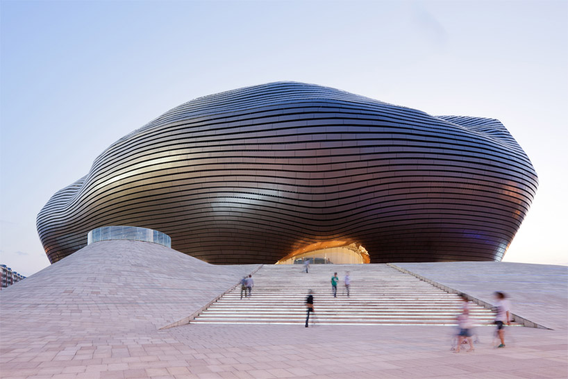 dutch photographer iwan baan has documented the recently completed and opened 'ordos museum' in ordos, china by<br />beijing-based practice MAD architects. situated at the create of a dune-like hill, the building appears to have landed<br />from another world into the recently created urban center within the once gobi desert. the masterplan is mindful of the existing<br />cultural traditions of the area while addressing the progress and future of the city, allowing the community to congregate and lounge<br />within the surrounding plazas. surfaced with metal panels, the undulating exterior protects the interior from the region's harsh winters<br />and sand storms.<br />upon entering the museum, an atrium with characteristics of a cave and canyon become apparent, introducing swaths of daylight<br />from above along with shadowed passages leading towards galleries. a series of bridges traverse the chasm from one void to another<br />guided by the changes in illumination. residents of the area may circulate through the interior to efficiently cross from one side of<br />the site to the other without entering exhibitions. employees of the center are provided a natural work environment with office and research spaces which flank a south-facing internal garden.