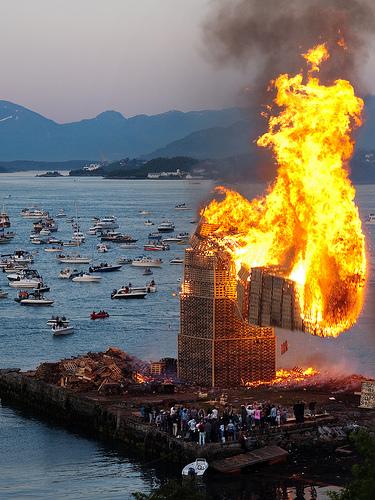 biggest bonfire in the world norway burning wood tower collapsing norway sea boats fjord hessa celebration slinningen alesund midsummer