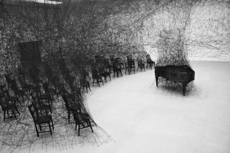 chiharu shiota - In silence installation When I first set my eyes on Japan-born, Berlin-based artist Chiharu Shiota's work, I wasn't sure if I was looking at an installation or a dark charcoal illustration. Though the piece echoes sketch-like imagery, it is in fact an installation piece involving a burnt piano in a room ravaged by black wool. The work known as In Silence is inspired by Shiota's own traumatic memories as a child, having witnessed her neighbor's house burn down. The charred piano is a direct memory of her neighbor's grand piano blazed up in smoke.  There is a melancholic aura that hovers throughout the incinerated room filled with singed furniture. The miles of thread woven in, around, and through each item within the space adds a feeling of entrapment. The way it engulfs the room's furnishings encapsulates the destructive and overwhelming nature of flames that have possessed one's material properties.