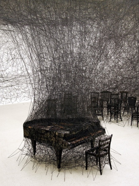 chiharushiotainsilence2 When I first set my eyes on Japan-born, Berlin-based artist Chiharu Shiota's work, I wasn't sure if I was looking at an installation or a dark charcoal illustration. Though the piece echoes sketch-like imagery, it is in fact an installation piece involving a burnt piano in a room ravaged by black wool. The work known as In Silence is inspired by Shiota's own traumatic memories as a child, having witnessed her neighbor's house burn down. The charred piano is a direct memory of her neighbor's grand piano blazed up in smoke.  There is a melancholic aura that hovers throughout the incinerated room filled with singed furniture. The miles of thread woven in, around, and through each item within the space adds a feeling of entrapment. The way it engulfs the room's furnishings encapsulates the destructive and overwhelming nature of flames that have possessed one's material properties.