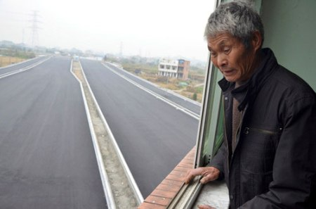 house highway china tearing down nail house province old retired couple resisting squatting demolition