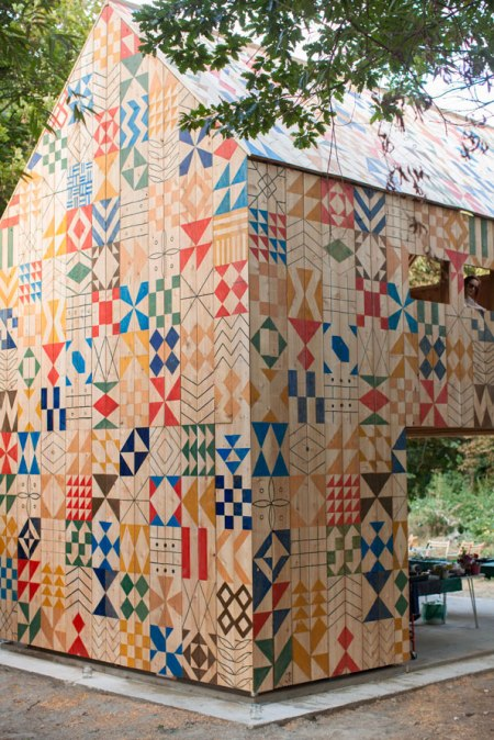 Ecology-of-Colour-by-Nous-Vous-and-Studio-Weave architecture facade patterns and motifs of geometrical colourful shapes on a facade, building sited at 'Ecology Island'