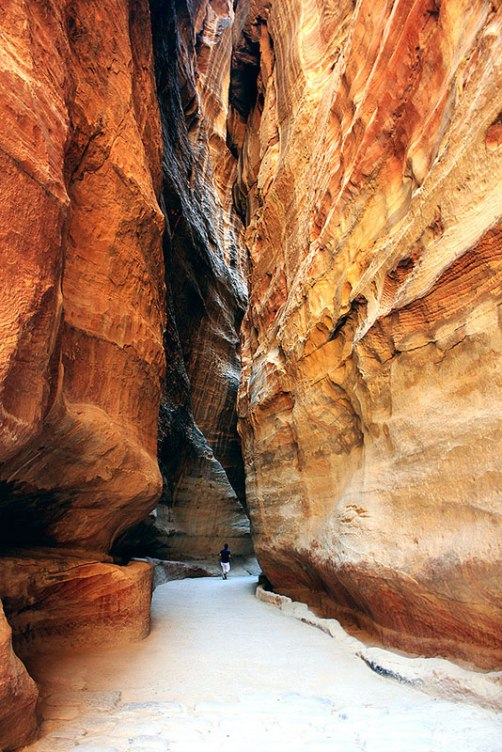 Photograph of a man walking in-between the stunning rock formations around the ancient Nabataean city of Petra, Jordan