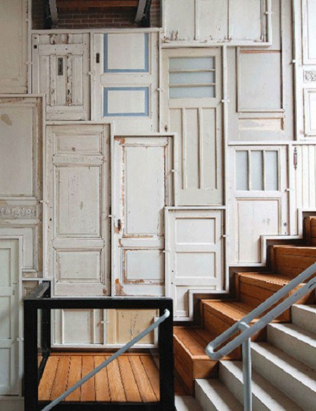 'Wall of Doors' - an interior wall composed of old, vintage, re-purposed white wooden doors by Dutch designer, Piet Hein Eek in an effort to preserve the memory of the old buildings that were torn down in order to build this new residential loft.