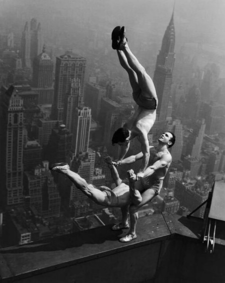 acrobats -balancing on the edge of a building / A stunning black and white photo capturing acrobats at the top of the Empire State Building performing the stunt during the opening of the building possibly on May 1, in the 1931.