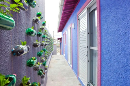 vertical-2 A transformation of an exterior wall in a small house outside Sao Paolo, by Rosenbaum. The wall has changed into a small vertical garden where series of cascading plastic bottles are hanging through strings.The plastic containers have been reused as planters filled with soil for different kinds of flowers, and medicinal herbs.