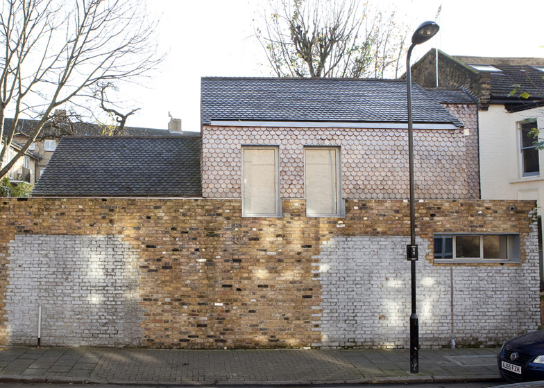 """Nicknamed the Gingerbread House by neighbours, the two-storey house sits behind the reconstructed wall of a former Victorian box factory and its tall windows overlap the mismatched brickwork...The architect drew inspiration from decorative vernacular architecture in Russia to design the cedar-shingle facade, then added windows framed by thick galvanised steel surrounds...To avoid overlooking neighbouring houses, all windows had to be placed on the north-facing street elevation, so Dewe Mathews also added a large skylight to bring in natural light from above...A double-height kitchen and dining room sits below this skylight on one side of the house and opens out to a small patio. The adjoining two-storey structure contains a living room on the ground floor, plus a bedroom, bathroom and small study upstairs.."""