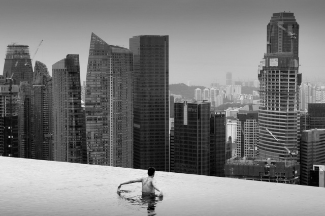 Beautiful black and white photograph of the Infinity Pool on-top of the 55storey Marina Bay Sands hotel in Singapore / unknown photographer  Located along the Marina Bay waterfront, Marina Bay Sands features three cascading hotel towers topped by an extraordinary sky park. At the top of the 55-storey hotel is a 150-meter infinity swimming pool, the world's largest outdoor pool at that height. Perched 191 metres above the ground, the pools are made up of 422,000 pounds of stainless steel and can hold 376,500 gallons (1424 cubic metres) of water.  With over 2,500 rooms and suites, Marina Bay Sand is currently the biggest hotel in Singapore.