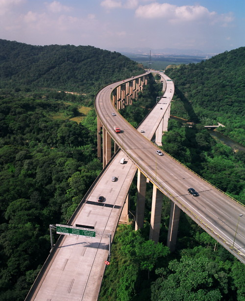 'Rodovia dos Imigrantes' - (official designation SP‑160) is a highway in the state of São Paulo, Brazil. The highway connects the city of São Paulo to the Atlantic coast and with the seaside cities of São Vicente and Praia Grande. It follows the route of Rodovia Anchieta and is also one of Brazil's busiest highways, especially on weekends.  Rodovia dos Imigrantes has 44 viaducts, 7 bridges, and 11 tunnels, along its 58.5 km stretch. The highway has recently been expanded, in one of the most audacious feats of Brazilian highway engineering, with extremely long tunnels and high strutting six-lane bridges constructed over the tropical rain forest which covers the steep faces of the Serra do Mar, the cliff range that separates the São Paulo plateau from the seaside lowlands. During sunny weekends, more than 1 million automobiles commonly cross its near 60 km run, separating the city of São Paulo from the sea. (Text: Wikipedia)