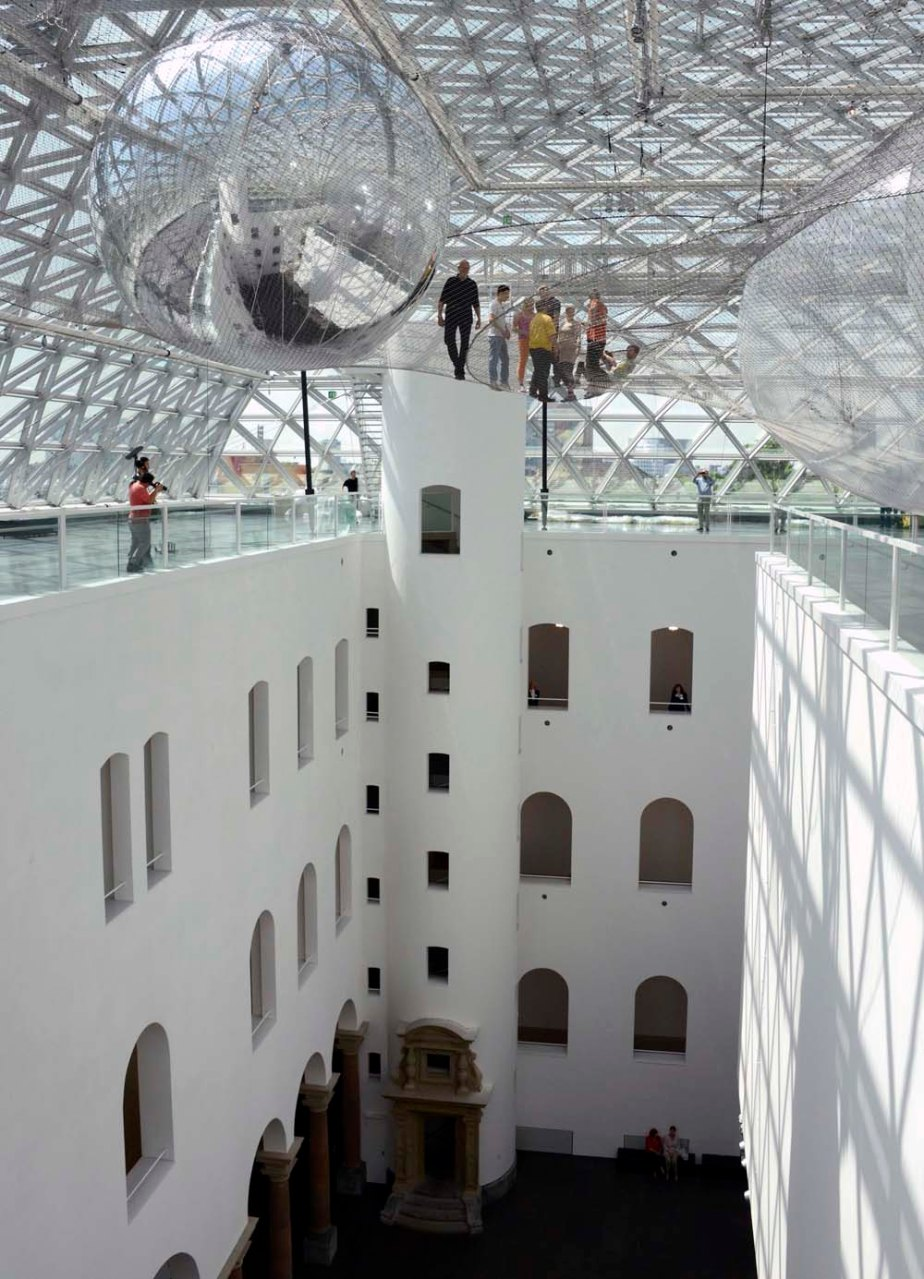 'In Orbit' ´wonderful suspended installation by Tomás Saraceno at the K21 Staendehaus museum in Duesseldorf, Germany.  Titled In Orbit the giant interactive piece is constructed from three separate levels of safety nets accessible from various points in the museum separated by enormous PVC balls measuring almost 30 feet (8.5 meters) in diameter. The resulting aerial landscape is an interesting hybrid between science fiction, spider webs, neural pathways and cloud formations.  Known for breaking the boundaries between art and science, Saraceno often refers to his interactive pieces as living organisms. In fact, over a period of three years Saraceno consulted with arachnologists (experts in the study of spiders), as well as architects and engineers to achieve the final design for In Orbit. Via the museum:      This floating spatial configuration becomes an oscillating network of relationships, resonances, and synchronous communication. When several people enter the audacious construction simultaneously, their presence sets it into motion, altering the tension of the steel wires and the intervals between the three meshwork levels. Visitors can coordinate their activities within the space, and are able – not unlike spiders in a web – to perceive space through the medium of vibration. Saraceno himself speaks of a new hybrid form of communication.