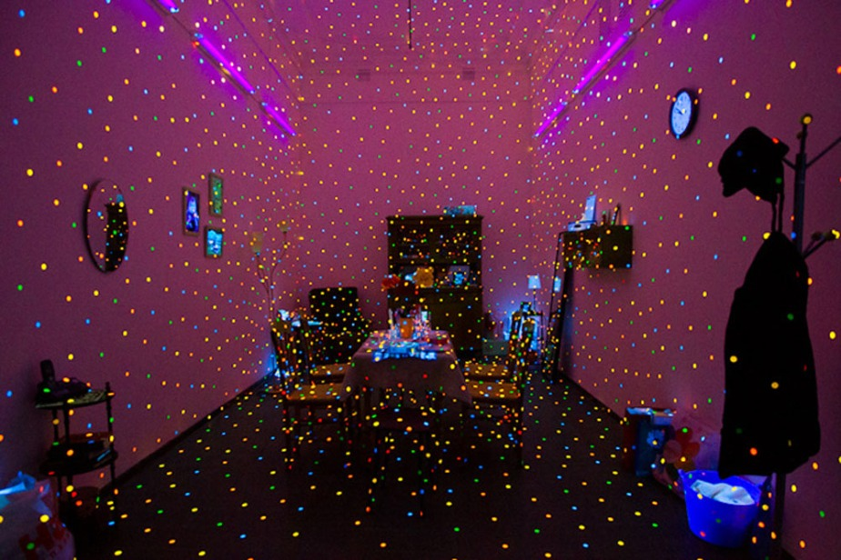 """I'm Here, but Nothing"" - black light art exhibition by Japanese artist Yayoi Kusama, 2000 using fluorescent sticker spots to fill an ordinary living room, giving the impression of a world seen through a magical, hallucinatory veil."