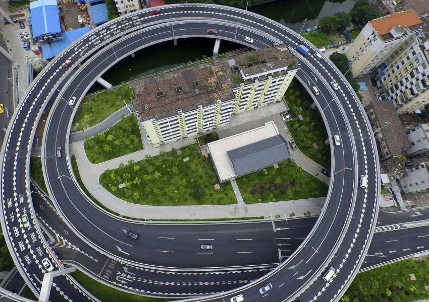An old residential building is seen surrounded by a newly-built ring viaduct, in Guangzhou